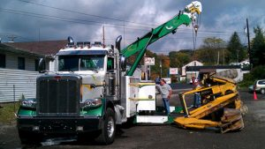 ferra's tow truck picking up a fallen over construction vehicle