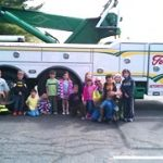 children posing for a picture in front of a tow truck
