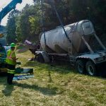 crane hoisting a semi truck out of a ditch