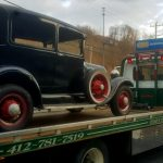 old car on a flatbed tow truck